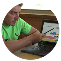 Camp instructor using a stylus to point to a presentation on notebook computer