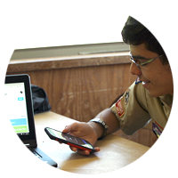 Boy scout checking information on his cell phone, while also using his laptop computer