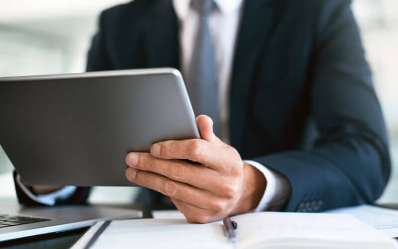 Businessman working in financial services company views reports on tablet device