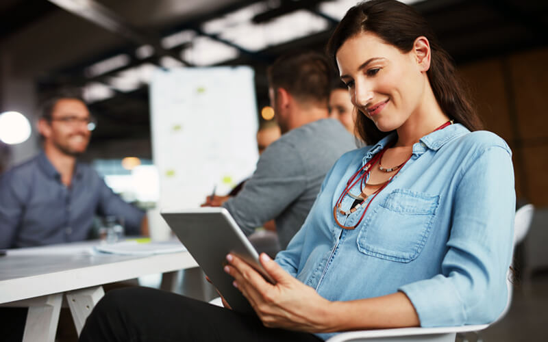 Smiling woman uses tablet sitting at desk in open office