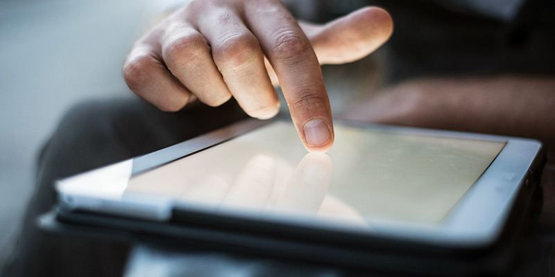 Close up of a hand of a businessman using tablet in cafe