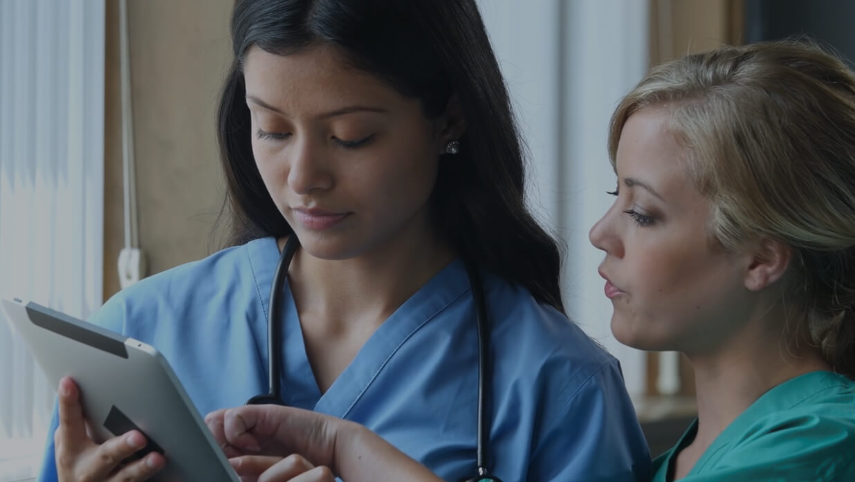 Two nurses discuss data on tablet