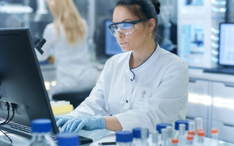 Female pharmacist on desktop computer in lab