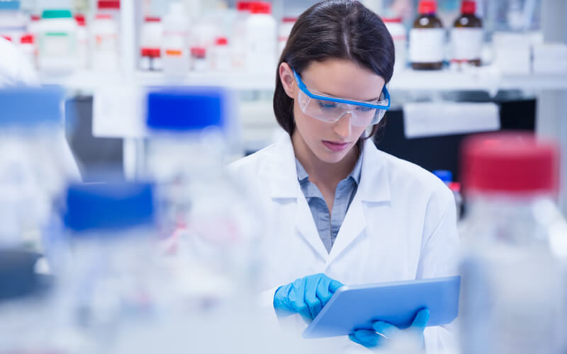 Female scientist works in lab surrounded by medication on tablet device
