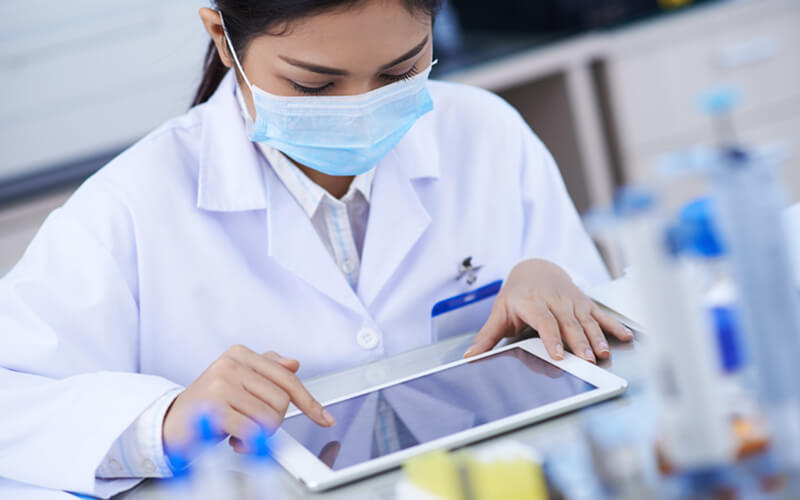 Female scientist works in lab with tablet device