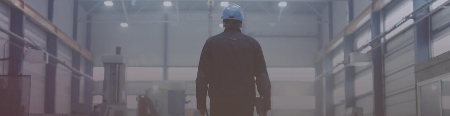 Factory worker walking down manufacturing plant