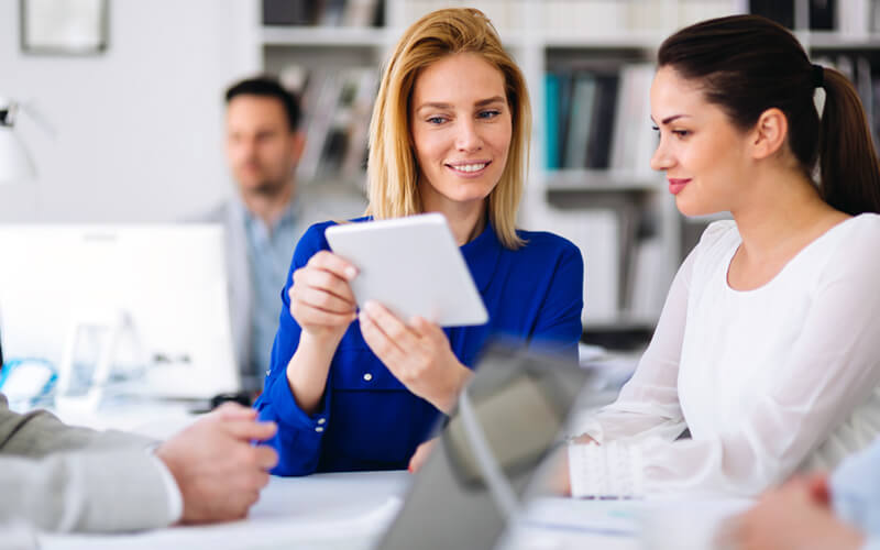 Smiling woman shares report on tablet with female colleague