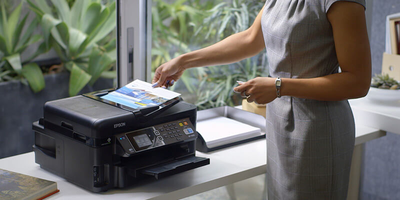 Business woman grabbing printed paper from Epson printer
