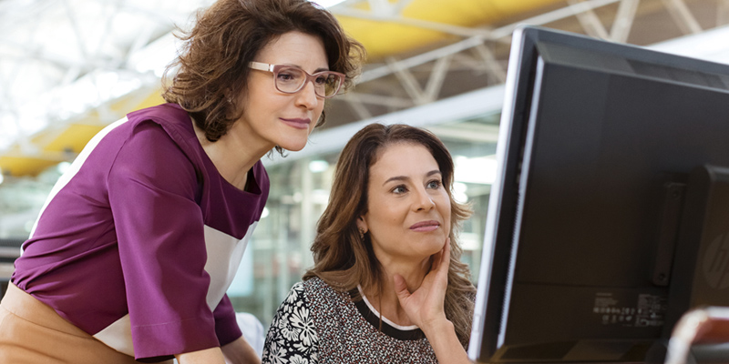 Two women looking at an HP EliteOne 800 AiO.