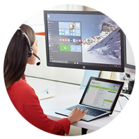 Woman on headset works on laptop and desktop computer