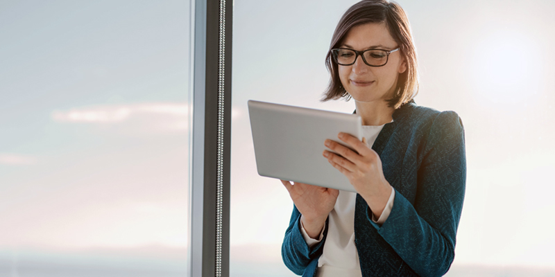 Business woman in front of windows looks at tablet device