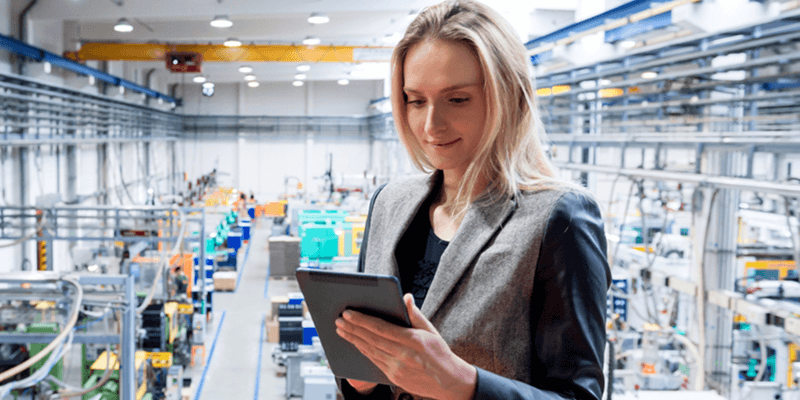 Female inspector looks over warehouse inventory using tablet device