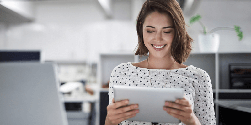 Smiling businesswoman works on tablet device