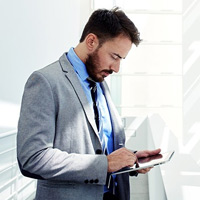 Business man using tablet to check email while off site
