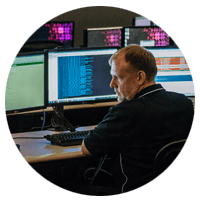 Security solutions manager reviewing company data remotely off dual computer monitors