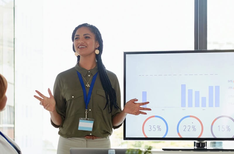 business-woman-presenting-infront-of-large-monitor