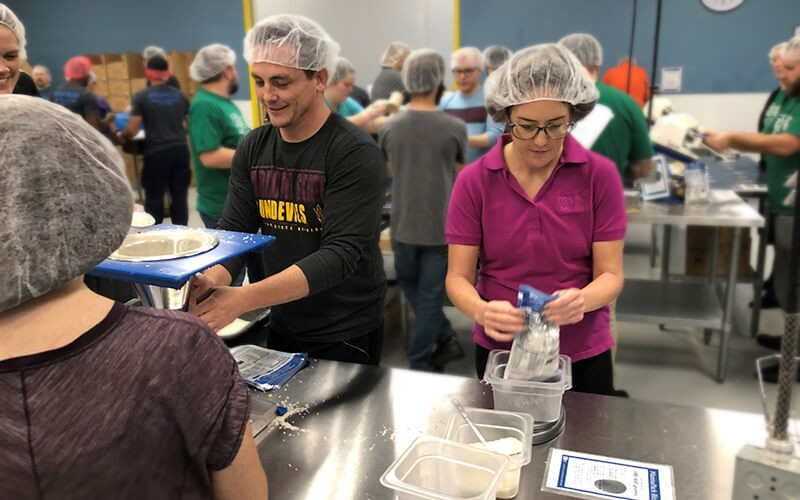 Insight teammates participate in packing food for Feed the Starving Children non-profit