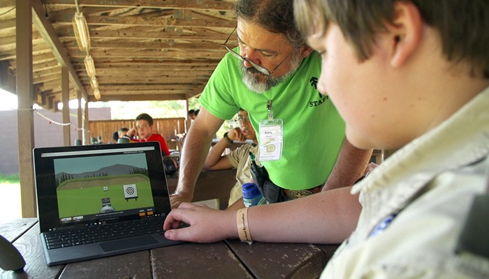 Camp instructor helping Boy Scout with hunting game on notebook computer