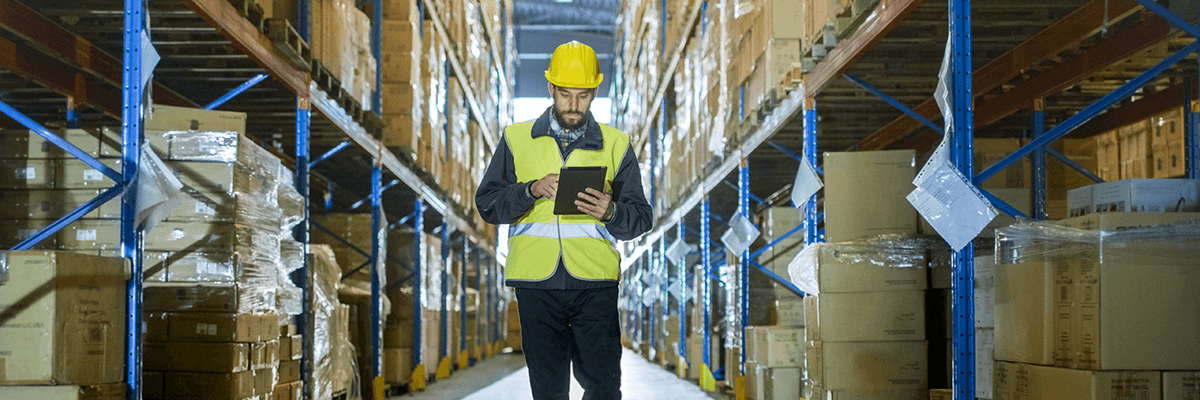Man with tablet works in distribution center warehouse