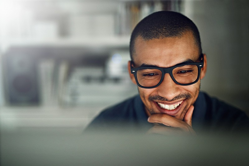 Smiling man in glasses reviews contacts on desktop computer