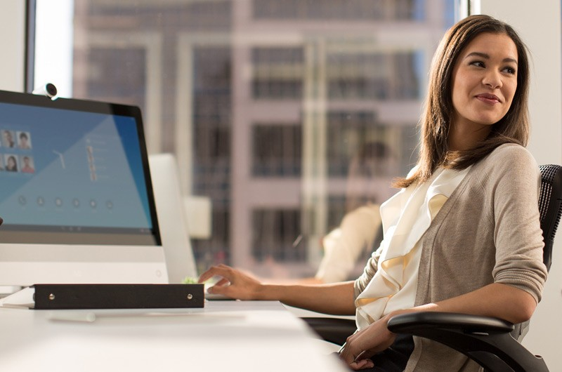 Young woman at desk with laptop reclining in her chair.