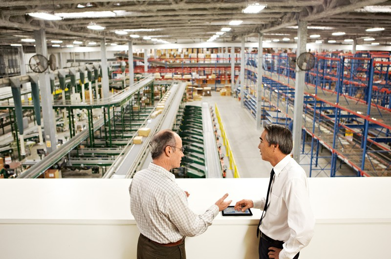 Two men in industrial warehouse talking.