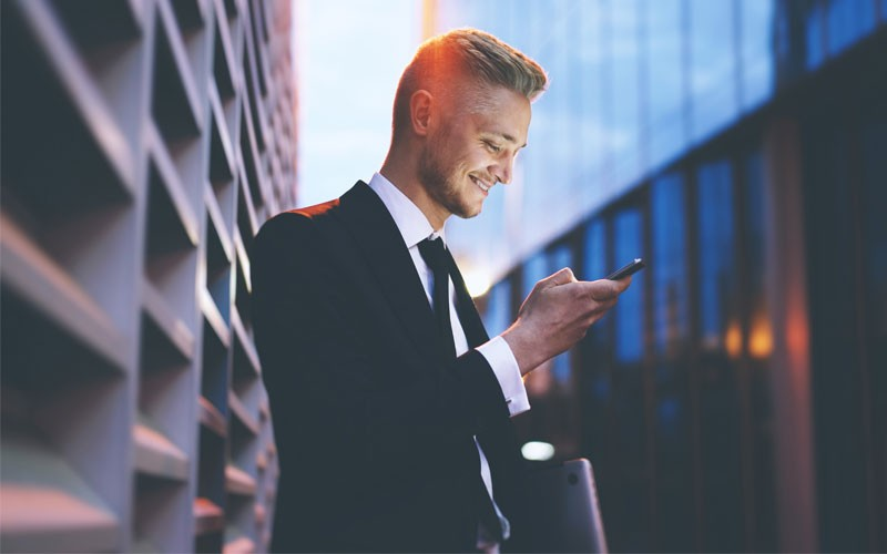 Business man using mobile device outside