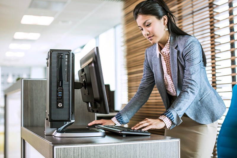 Receptionist leaning over front desk using the HP ProDesk 400 SFF G1 on IWC stand