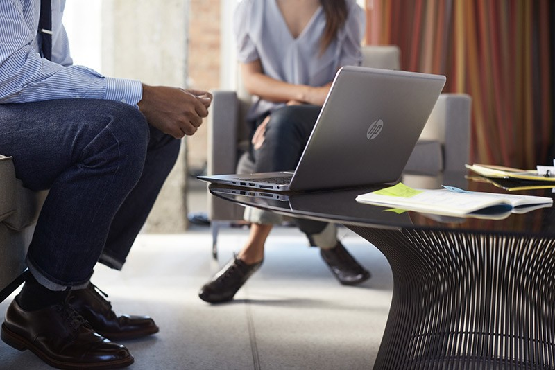 A man and woman having a meeting at work using a HP EliteBook 1040 G3.