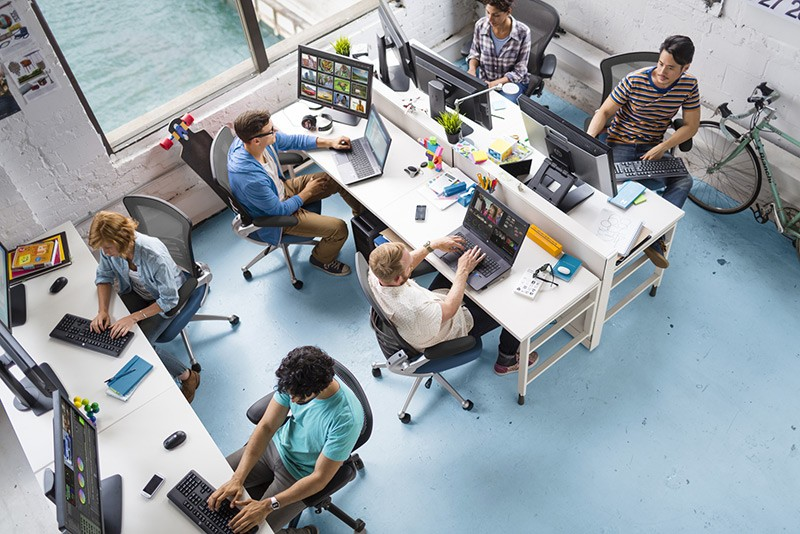 Overhead view of creative professionals working in an office with various HP workstations and displays.