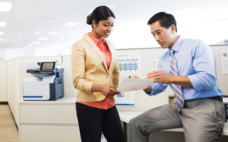 Business professionals have a discussion near a HP LaserJet Enterprise color flow MFP M575c
