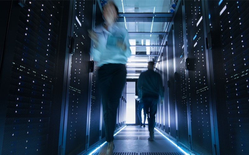 Two people walking through data center