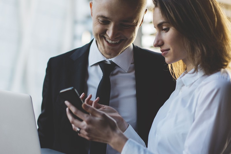 Business man and woman looking at content on smart phone.