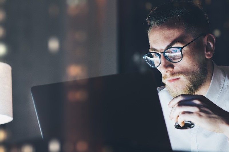 Business man with glasses working late in office looking at laptop
