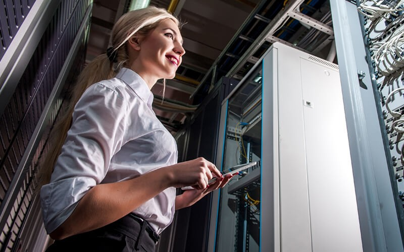 Smiling IT administrator on tablet in server rack room