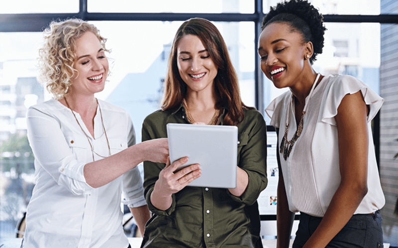 Three business women in front of open office window on tablet device