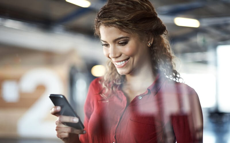Smiling woman uses mobile phone in modern workplace
