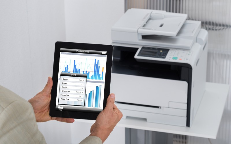 Woman holding tablet with data up in front of printer