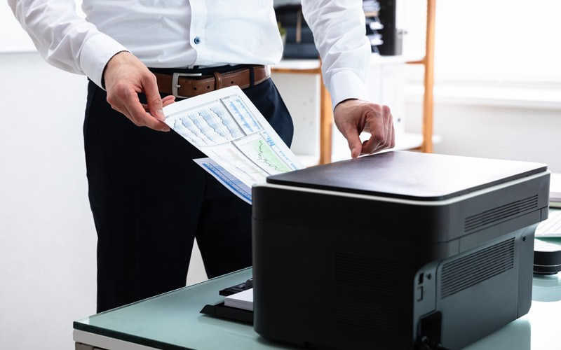 Businessman printing off graph from printer