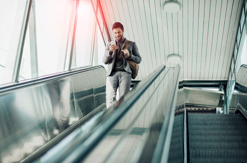 Business executive using mobile app on smart phone on escalator