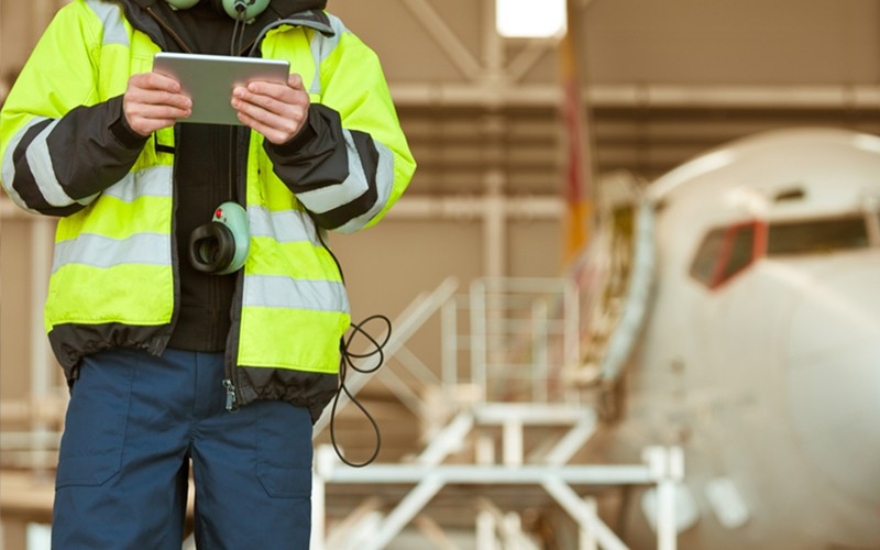 Aircraft engineer uses tablet device in front of airplane in hangar
