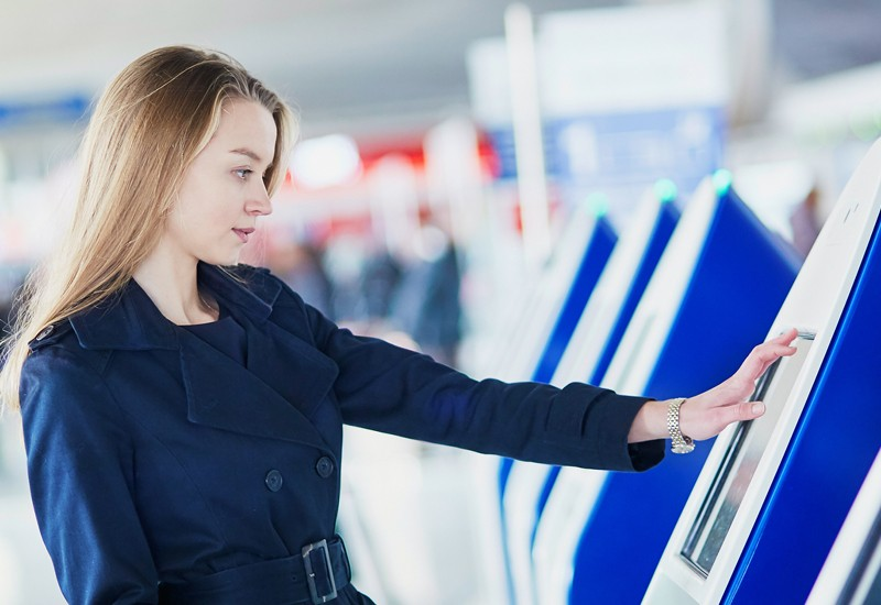 Business woman using touch screen on kiosk device