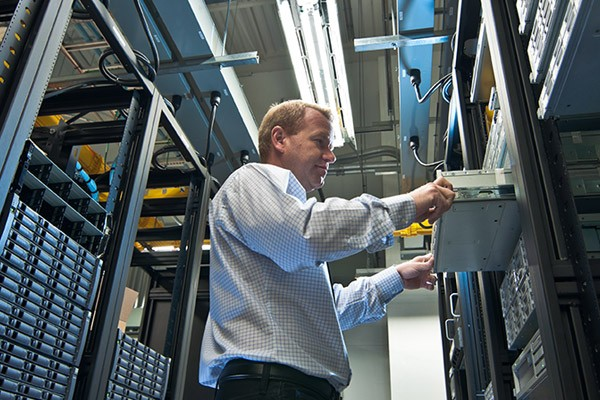 IT technician replaces server in data center