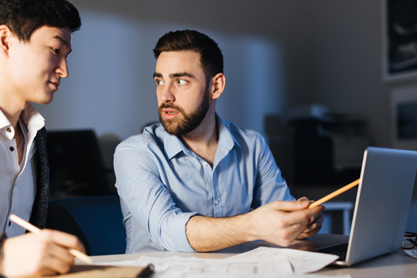 Two IT professionals creating networking strategy in office at night
