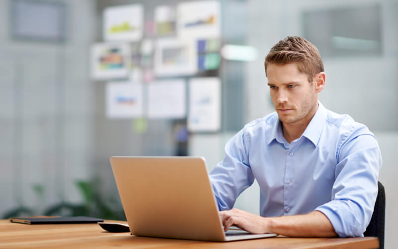 Businessman on laptop computer in bright open office space