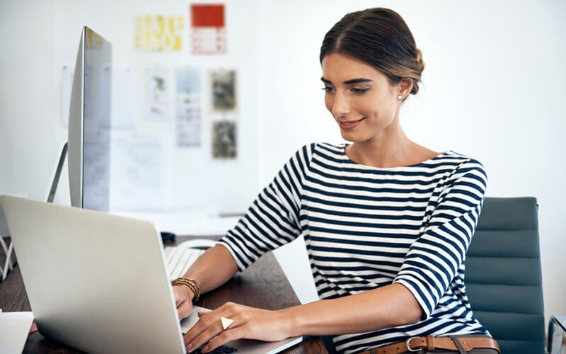 Smiling woman on laptop computer in open office