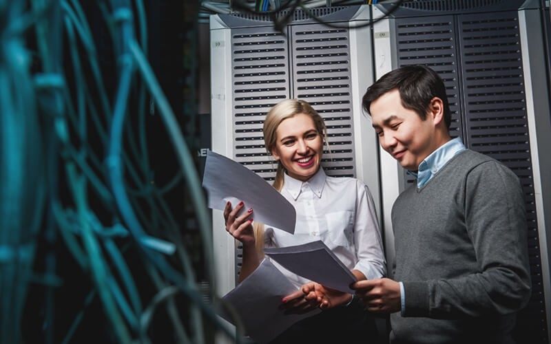 Business employees in server room