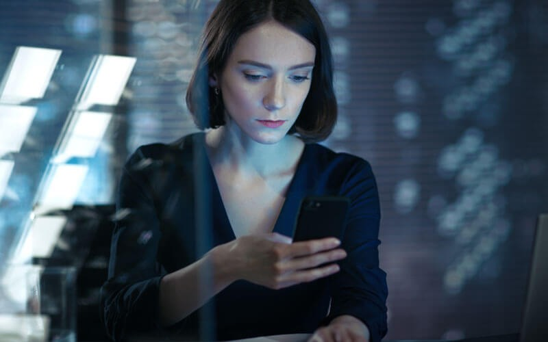 Business woman reading data off of smart device