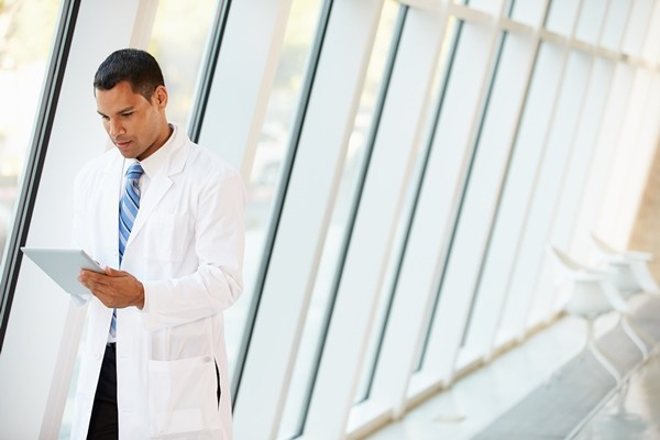 Doctor on tablet in hallway of hospital