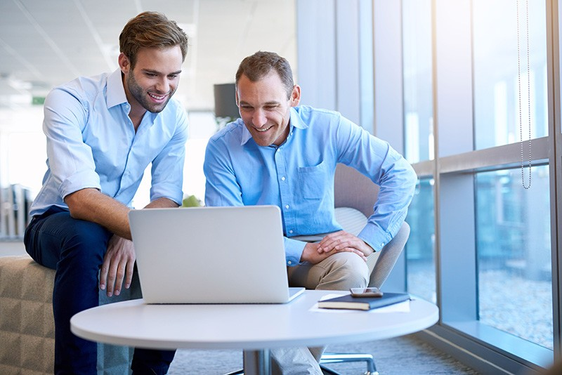 Two men looking at laptop smiling in front of coffee table